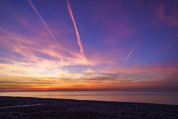 Чарующее градиентное небо со следами самолета после захода солнца на море