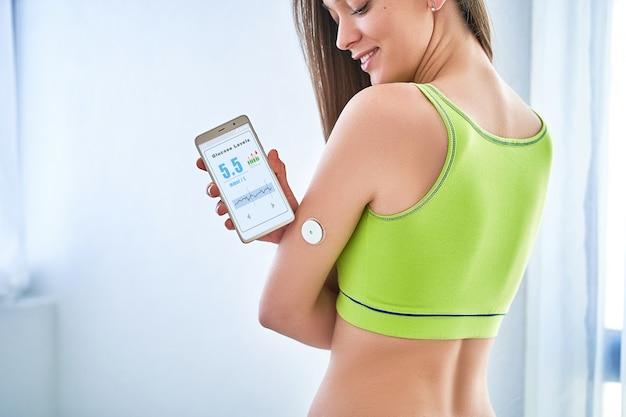 糖尿病患者がリモートセンサーとスマートフォンでグルコースレベルをチェックします。
