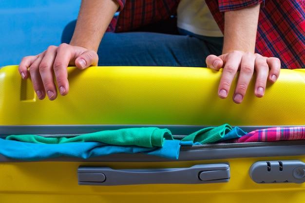 黄色のスーツケースに服を梱包します。旅行や出張に必要なものを梱包してください。休暇、休日。旅行のコンセプト