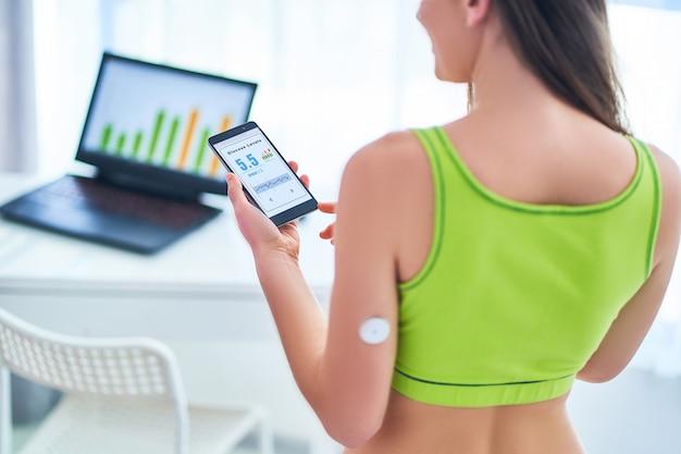糖尿病患者の制御とリモートセンサーと携帯電話によるグルコースレベルのチェック。
