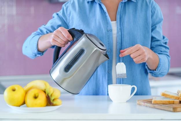 Женщина кладет чайный пакетик в чашку и использует электрический чайник для приготовления горячего чая дома на кухне