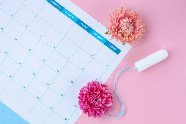 定期的な月経周期。タンポン、女性のカレンダー、花。重要な日の衛生管理。女性および婦人科医療。