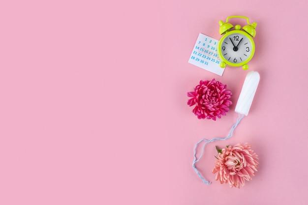 月経用タンポン、目覚まし時計、女性用カレンダー、ピンクの花。重要な日の衛生管理。定期的な月経周期。