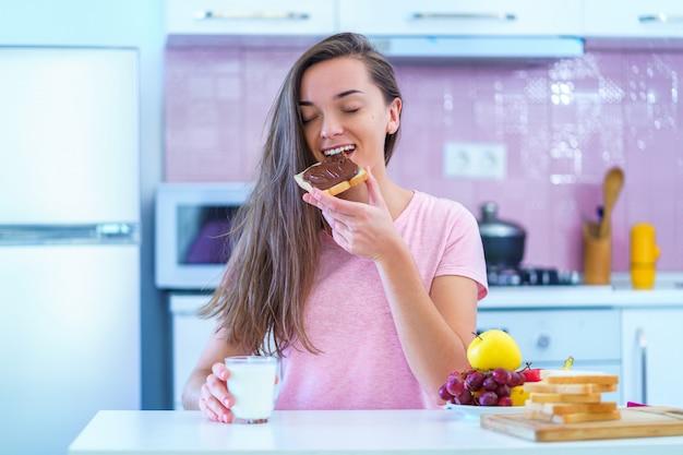 Счастливая радостная молодая женщина завтрака ест тостовый хлеб с ореховым шоколадным кремом на десерт дома