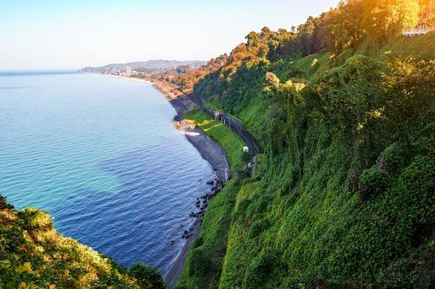 Красивый, чарующий вид на синее море, зеленый мыс и железную дорогу из ботанического сада в батуми грузия в ясный солнечный день
