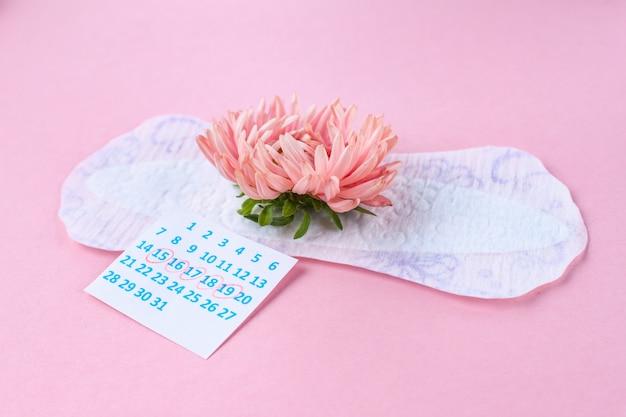 重要な日のための女性用の生理用ナプキンとピンクの花。月経中の衛生管理。定期的な月経周期。毎月の保護