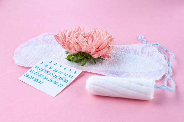 月経用のパッドとタンポン、女性用カレンダー、ピンクの花。重要な日の衛生管理。定期的な月経周期。