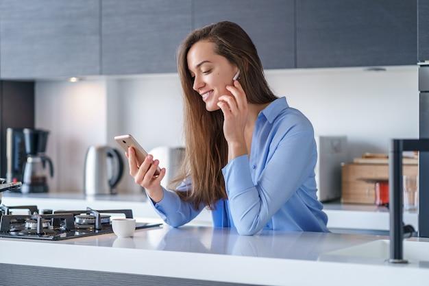 スマートフォンとワイヤレスヘッドフォンを使用して、自宅のキッチンで音楽を聴いたりビデオ通話をしたりする若い幸せな女性。現代のモバイルピープル