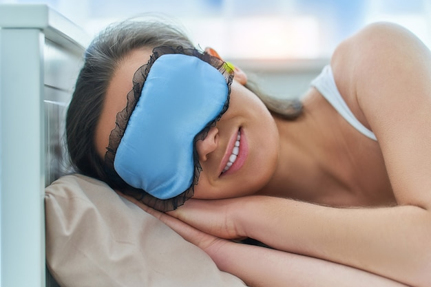 Молодая брюнетка, используя затычки для ушей и маску для глаз для лучшего сна и сладких снов в спальне