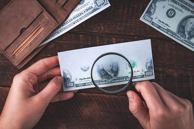 偽造者は紙幣を偽造します。偽のコンセプト。偽のお金、アメリカドルの財布、拡大鏡。上面図