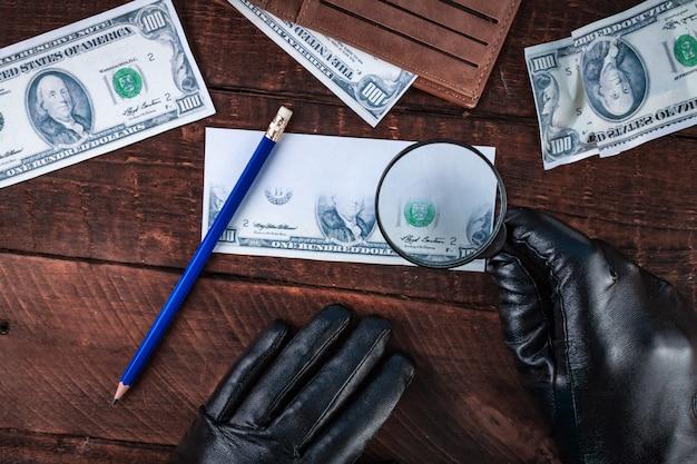 黒い手袋の偽造者が紙幣を偽造します。偽のコンセプト。偽のお金、アメリカドルの財布、拡大鏡。上面図