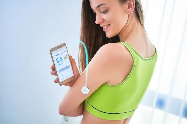 女性糖尿病患者は、リモートセンサーとスマートフォンでグルコースレベルを制御およびチェックします。血液なしでブドウ糖レベルを監視する。糖尿病治療、医療におけるデジタル医療技術