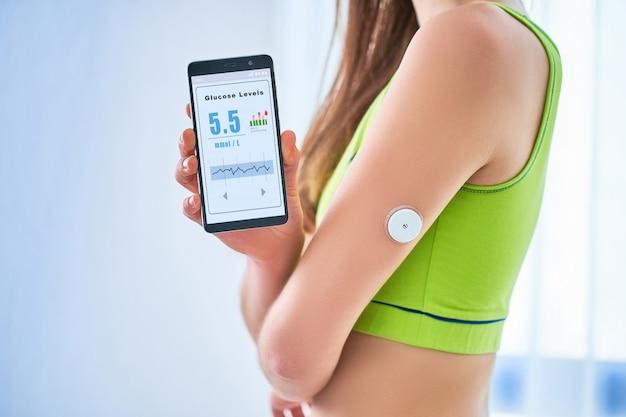 女性の糖尿病患者は、リモートセンサーと携帯電話で血糖値を制御およびチェックしています。血のないブドウ糖のレベルを継続的にオンライン監視します。糖尿病治療におけるデジタル医療技術