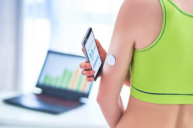 女性の糖尿病患者は、リモートセンサーと携帯電話で血糖値を制御およびチェックしています。デジタルブドウ糖メーターを使用して血なしでブドウ糖のレベルをオンライン監視します。糖尿病治療の技術
