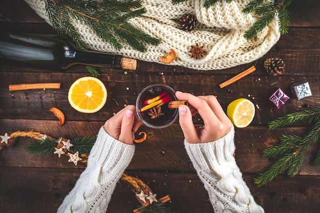 Молодая женщина в теплом, вязаном, белом пуловере держит на рождество горячий глинтвейн в бокале со специями и цитрусовыми фруктами. уютный, зимний вечер. зимние напитки. плоская планировка, вид сверху.