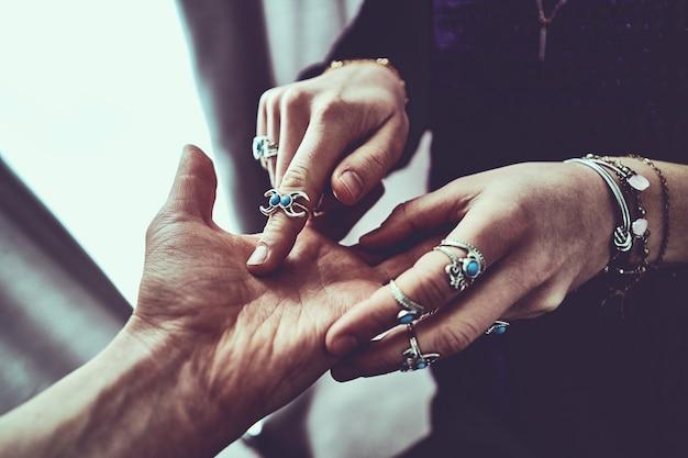 ターコイズブルーの石とブレスレットで銀の指輪を身に着けている占い師の女性は、占いの間に手のひらラインを読み、未来を予測します。手相占いと神秘的な占い
