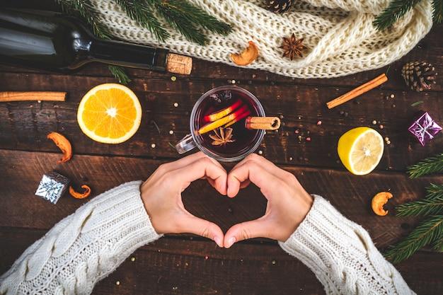 お気に入りのホットな冬の飲み物。スパイスと柑橘系の果物とグリューワインのカップ。冬の飲み物。
