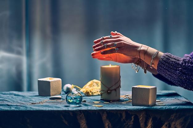 神秘的な魔法と占いの間に魔法の呪文にキャンドルの炎を使用する魔女の女性