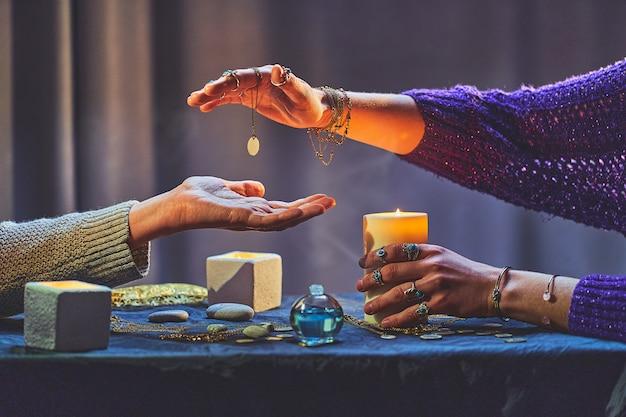 手相占いやキャンドルや他の魔法のアクセサリーの周りの占いの間に魔法の占い師の女性