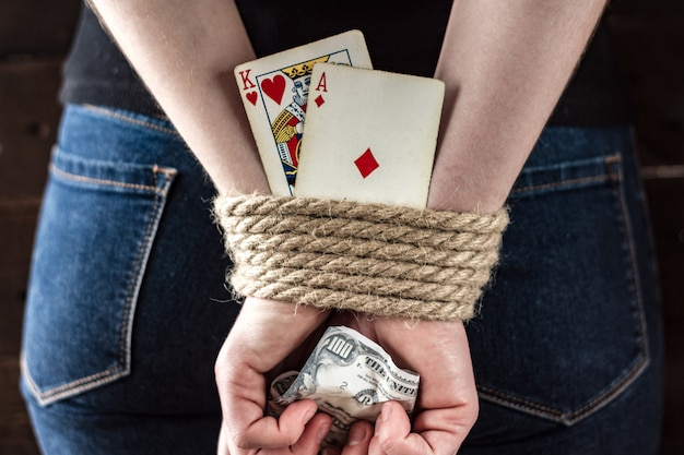 Карточная зависимость. зависимость от покера, азартных игр. молодая женщина со связанными руками держит игральные карты. концепция азартных игр