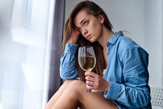 シャツに悲しそうな目を持つ若い動揺落ち込んで孤独な物思いにふける女性は白ワインのガラスを保持し、不況と心配の間に家の窓際で一人で座っています。