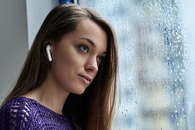 ワイヤレスイヤホンを持つ若い物思いにふける女性音楽愛好家は、秋の雨の雨の滴と窓際に立っている間になだめるような落ち着いたリラックスできる音楽を聴きます
