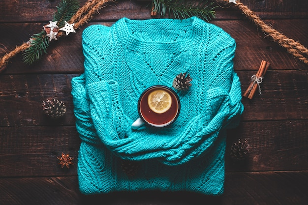 暖かいセーター、松ぼっくり、レモン、シナモン、アニスの星が入ったマグカップ。冬の服と飲み物。冬のコンセプト。