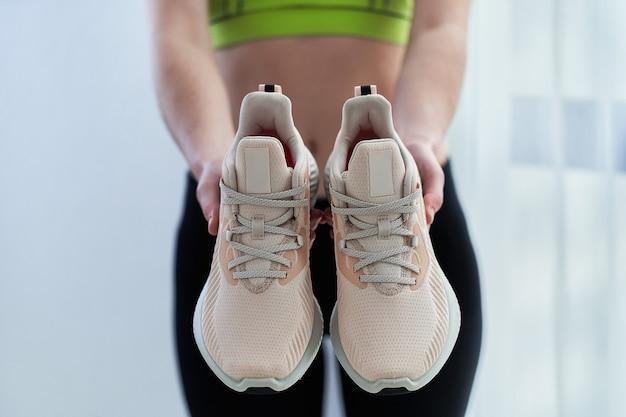 Спортивная (ый) женщина в спортивной одежде держит бежевые кроссовки для бега и тренировки. занимайтесь спортом и будьте в форме. спортивные люди со здоровым спортивным образом жизни