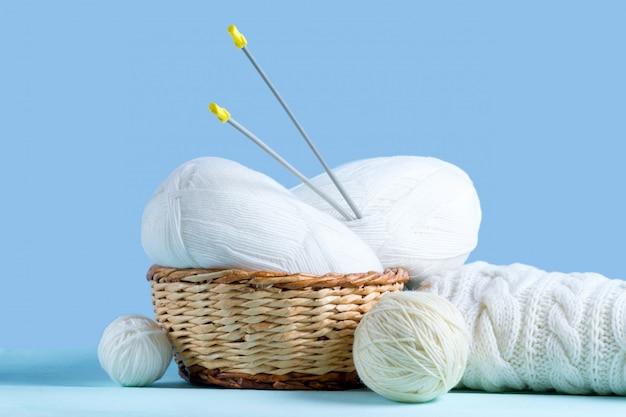 Белые нитки для вязания, спицы и белый вязаный свитер. концепция вязания. трикотажная и зимняя одежда
