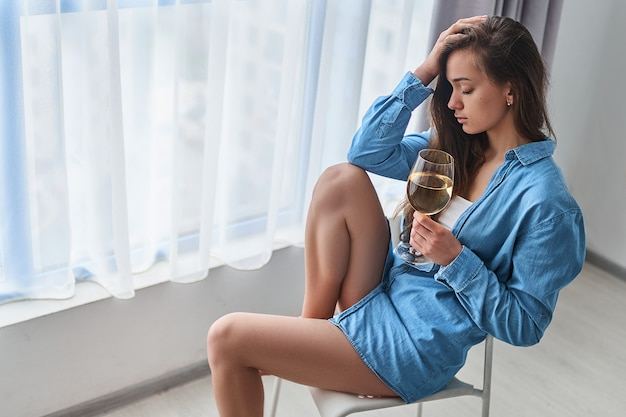 目を閉じてアルコール依存症に苦しんでいる白ワインのガラスを飲む孤独な女性は頭を抱えており、困難な生活の問題やうつ病の間に家の窓際の近くに一人で座っています。