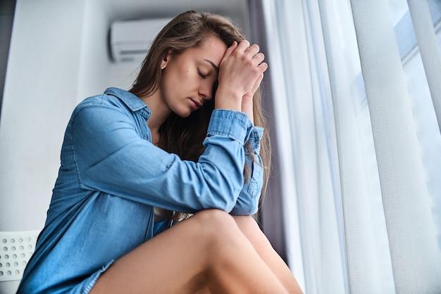 Молодая расстроенная грустная подавленная подчеркнутая женщина подросток сидит одна дома и держит голову в руках во время депрессии, трудностей, проблем и забот о жизни