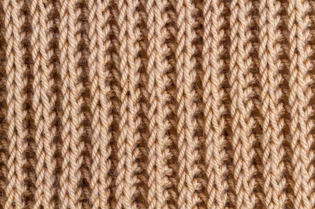 Текстура коричневой вязаной пряжи. трикотажная и зимняя одежда