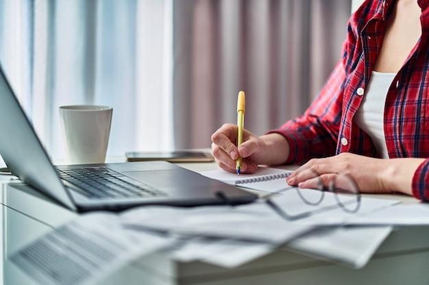 ノートパソコンでオンラインで作業し、ノートにデータ情報を書き留める女性。自宅で遠隔学習中の女性