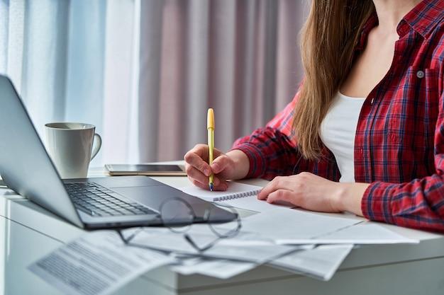 ラップトップでリモートで作業し、ノートブックの乳製品に重要な情報を書き留めている女性ブロガー。自宅で遠隔教育とオンラインコースを学習中の女性