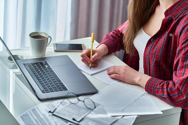 ノートパソコンで作業し、ノートブックの乳製品に重要なデータ情報を書き留める女性ブロガー。自宅で勉強する遠隔教育およびオンラインコース中の女性