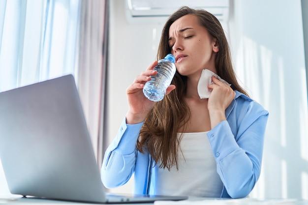 暑い天候と喉の渇きに苦しんでいる汗をかく働く女性は、夏の日に自宅のコンピューターでオンラインリモート作業中に彼の首をナプキンで拭きます。