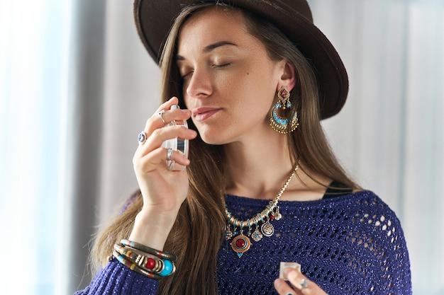 Стильная, модная, привлекательная брюнетка с закрытыми глазами, одетая в бижутерию и шляпу, наслаждается ароматом духов