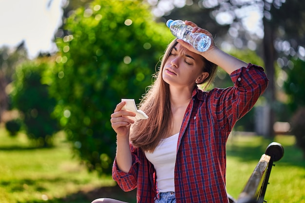 Потливая женщина отдыхает на скамейке и охлаждается бутылкой холодной освежающей воды в парке в жаркую летнюю погоду
