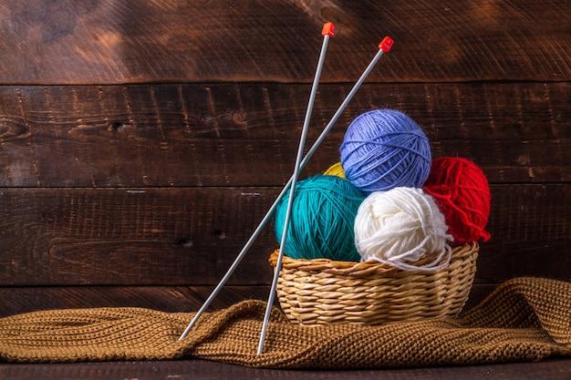 編み物、ニットスカーフ、暗い背景に編み針の色糸。コピースペース。編み物