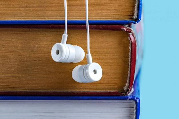 オーディオブックのコンセプト。白いヘッドフォンと本。仕事を見上げずに本を読む