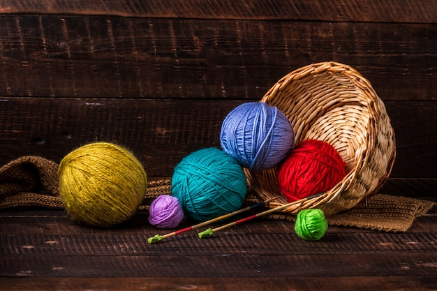 暗い色の木製の背景に編み物を作るための明るい色の糸。編み物