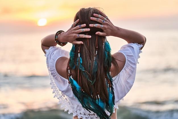 Богемная хиппи женщина с синими перьями в волосах