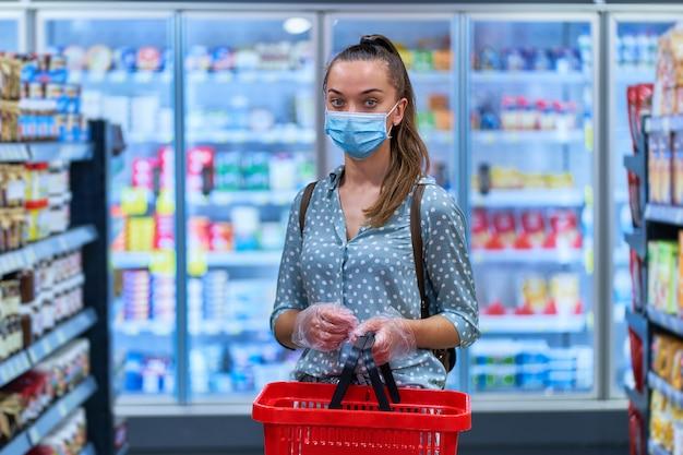 Портрет женщины-покупателя в защитной маске и прозрачных перчатках с корзиной для покупок среди полок в продуктовом магазине