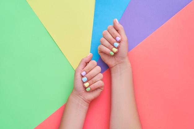 カラフルな背景に明るい色で女性の手