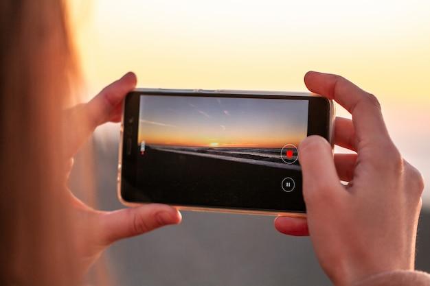 若い女性がビーチで夕日を撮影します。