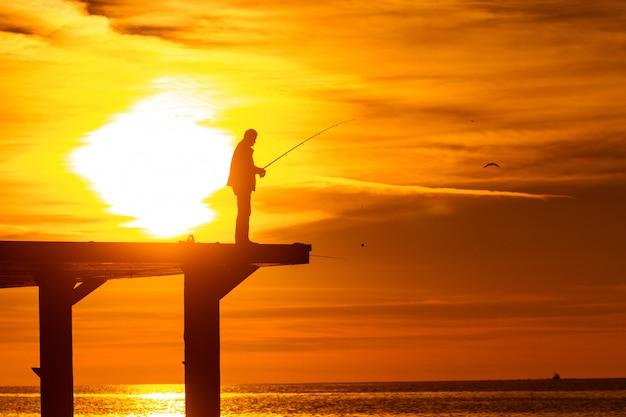 Рыбак, ловящий рыбу в море на пирсе на закате