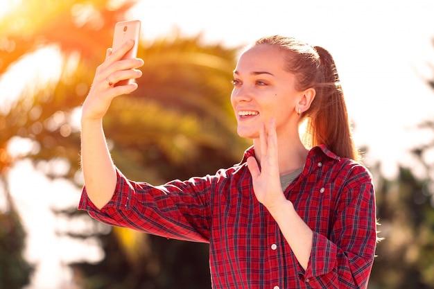 美しい若い笑顔の女性が電話で通信します