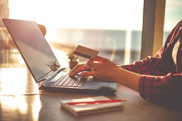 オンラインビジネスの夕暮れ時の窓にテーブルの上のノートパソコンとホームオフィスで居心地の良い職場