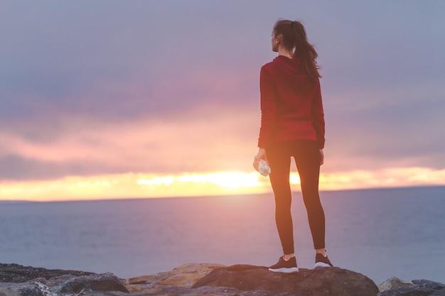 石の上に立って、水のボトルを保持していると日没で海を背景にトレーニングの後休んでいるスニーカーのフィットネス女性