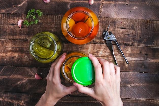 Домашние соленья баночки свежих огурцов, сочные помидоры, сладкие кабачки на деревянном фоне.